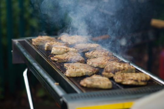 delicious steaks cooking on a barbecue at an event