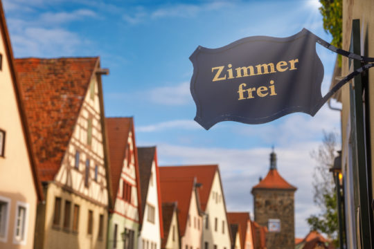 Zimmer frei (Rooms available) sign at a guesthouse or hotel with Half-timbered houses in background. Accommodation during travel by Romantic Road touristic route in Bavaria, Germany concept